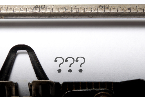 Typewriter with question marks on the page