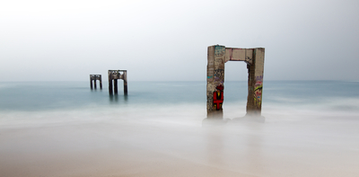 A mysterious scene of ruined stone piers stretching into a foggy sea.